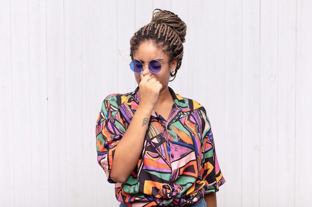 Jeune femme afro se sentant dégoûtée, tenant le nez pour éviter de sentir une odeur nauséabonde et désagréable
