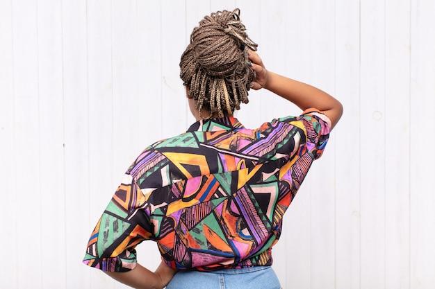 Jeune femme afro se sentant désemparée et confuse, pensant à une solution, avec la main sur la hanche et d'autres sur la tête, vue arrière