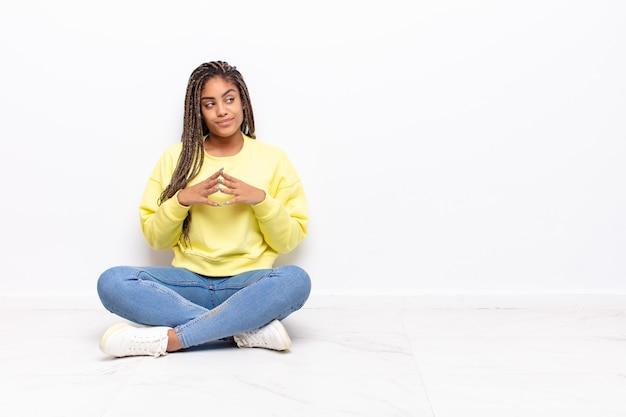 Jeune femme afro se sentant fière, espiègle et arrogante tout en élaborant un plan diabolique ou en pensant à un truc