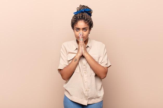 Jeune femme afro se sentant inquiète, pleine d'espoir et religieuse, priant fidèlement isolée