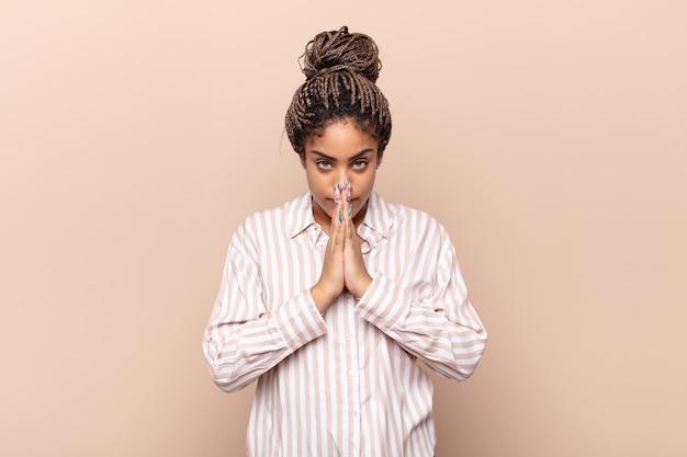 Jeune femme afro se sentant inquiète, pleine d'espoir et religieuse, priant fidèlement avec les paumes pressées, implorant pardon
