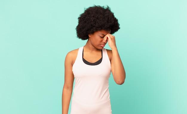 Jeune femme afro se sentant stressée, malheureuse et frustrée touchant le front et souffrant de migraines de maux de tête sévères