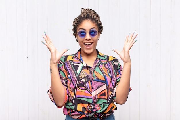 Jeune femme afro se sentir heureuse, émerveillée, chanceuse et surprise, célébrant la victoire avec les deux mains en l'air