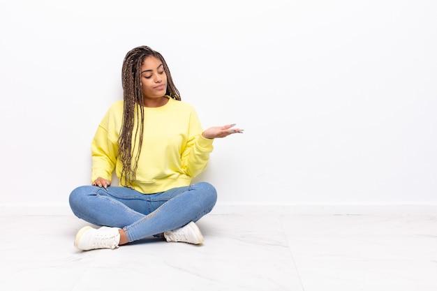 Jeune femme afro se sentir heureuse et souriante avec désinvolture, à la recherche d'un objet ou d'un concept tenu sur la main sur le côté