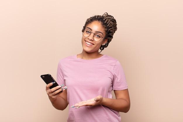 Jeune femme afro souriant joyeusement, se sentant heureuse et montrant un concept dans l'espace de copie avec la paume de la main.