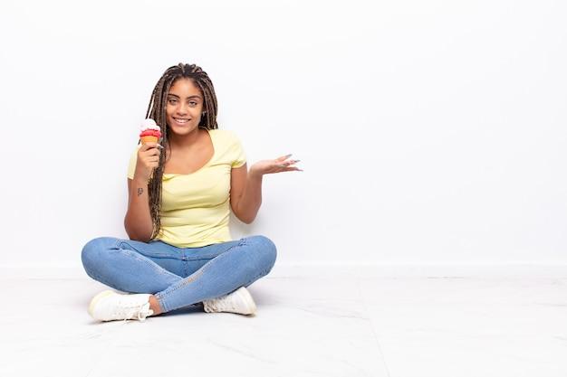 Jeune femme afro souriant joyeusement, se sentir heureux et montrant un concept dans l'espace de copie avec la paume de la main
