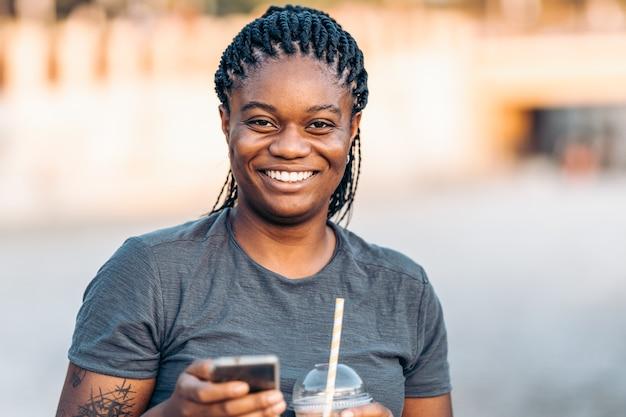 Jeune femme afro souriante à la caméra avec un téléphone portable et une poignée de main dans la rue.