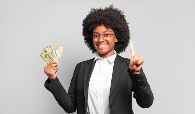 Jeune femme afro souriante et à la recherche amicale, montrant le numéro un ou en premier avec la main en avant, compte à rebours. concept d'entreprise