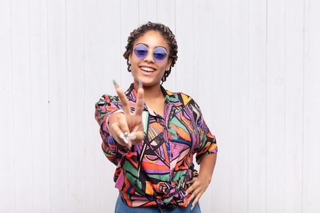 Jeune femme afro souriante et à la recherche heureuse, insouciante et positive, gesticulant la victoire ou la paix d'une seule main