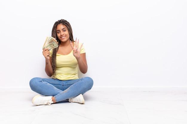 Jeune femme afro souriante et semblant amicale, montrant le numéro quatre ou quatrième avec la main en avant, compte à rebours. notion d'argent
