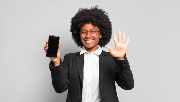 Jeune femme afro souriante et à la sympathique, montrant le numéro cinq ou cinquième avec la main en avant