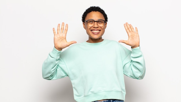 Jeune femme afro souriante et à la sympathique, montrant le numéro dix ou dixième avec la main en avant, compte à rebours
