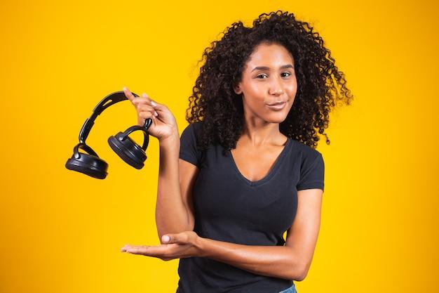 Jeune femme afro tenant un casque sur fond jaune. concept de musique et de divertissement