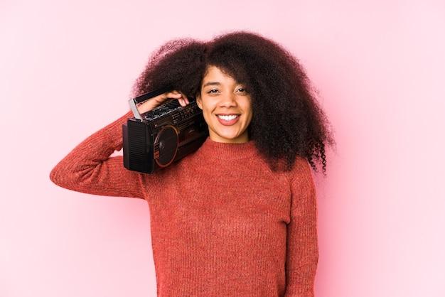 Jeune femme afro tenant un cassete isolé heureux, souriant et joyeux.