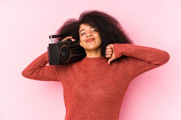 Jeune femme afro tenant une cassete isolée se sent fière et confiante, exemple à suivre.