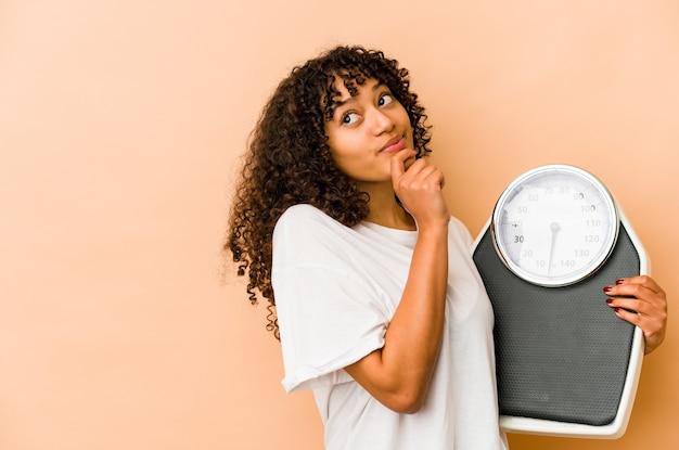 Jeune femme afro tenant une échelle à la recherche de côté avec une expression douteuse et sceptique