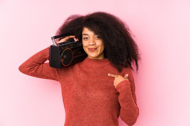 Jeune femme afro tenant une personne isolée cassete pointant à la main vers un espace de copie de chemise, fier et confiant