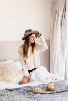 Jeune femme, agenouillement, sur, lit, porter, chapeau, à, fruits sains, sur, lit