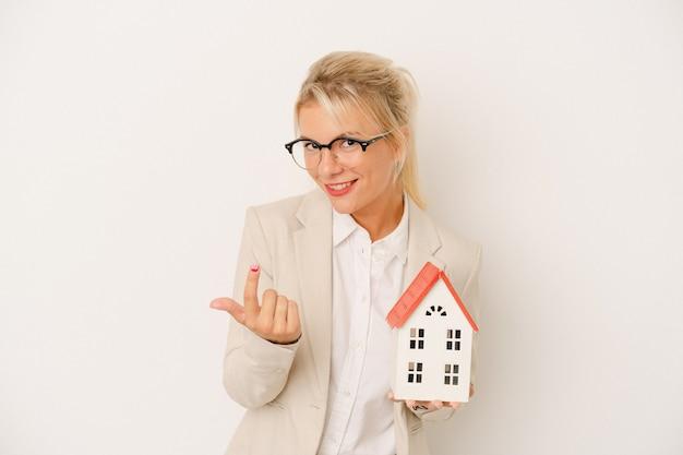 Jeune femme d'agent immobilier tenant un modèle de maison isolé sur fond blanc pointant du doigt vers vous comme si vous vous invitiez à vous rapprocher.