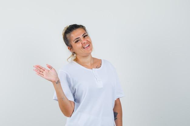 Jeune femme en agitant la main pour dire au revoir en t-shirt et à la bonne humeur