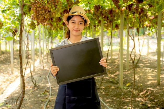 Jeune femme d'agriculteur d'asie tenant un tableau noir dans un vignoble de raisins, concept de fruits biologiques sains.
