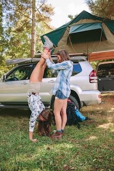Jeune femme aidant à son amie faisant le poirier dans un camping dans la forêt. concept de temps libre et de plaisir.