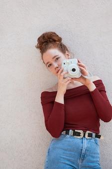 Jeune femme à l'aide d'un appareil photo vintage