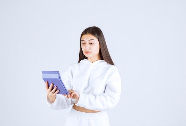 Jeune femme à l'aide d'une calculatrice sur fond blanc-gris.