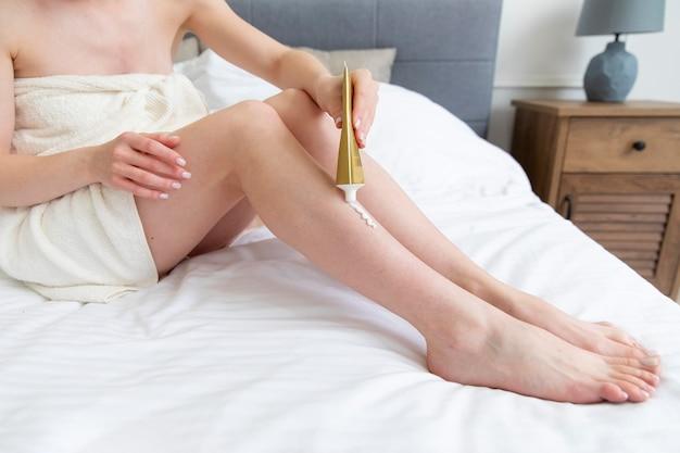 Jeune femme à l'aide d'une crème pour les jambes