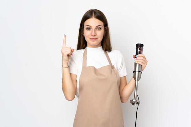 Jeune femme à l'aide d'un mélangeur à main isolé sur blanc pointant avec l'index une excellente idée