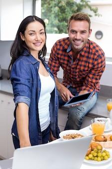 Jeune femme à l'aide d'un ordinateur portable et homme à l'aide d'une tablette numérique