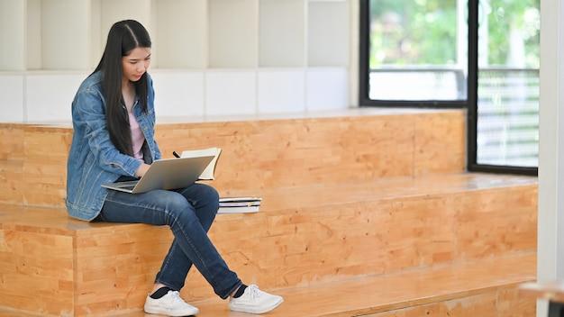 Jeune femme à l'aide d'un ordinateur portable et de lire le cahier dans la salle de la bibliothèque.