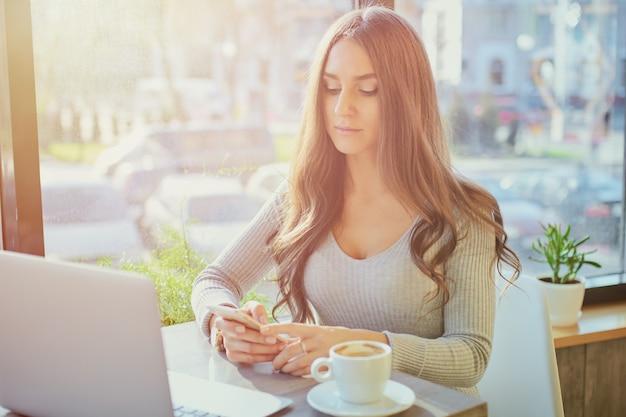 Jeune femme à l'aide de portable et d'ordinateur portable au bureau ou au café. concept de travail à distance