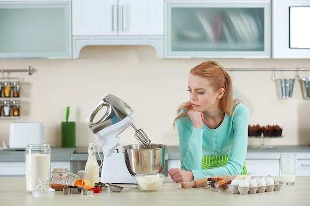 Jeune femme à l'aide d'un robot culinaire pour faire une pâte