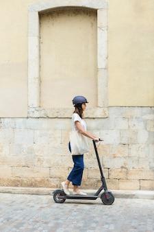 Jeune femme à l'aide d'un scooter écologique