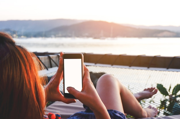Jeune femme à l'aide de smartphone avec écran blanc tout en se trouvant côté mer avec coucher de soleil du soir.