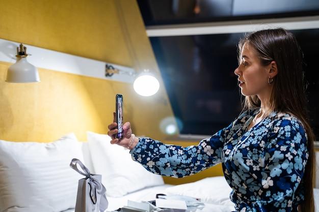 Jeune femme à l'aide de smartphone. heureux souriant belle fille sur le lit dans la chambre prend selfie