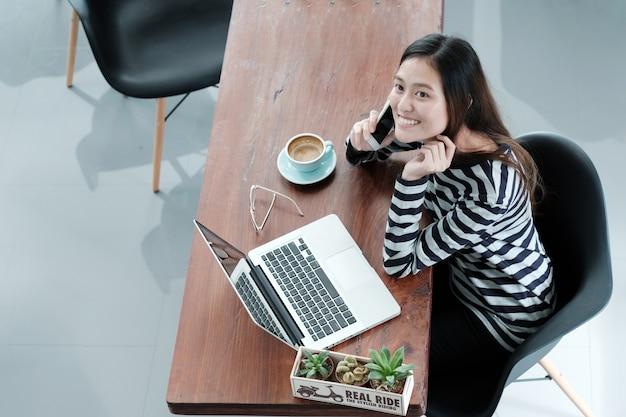 Jeune femme à l'aide de smartphone et ordinateur portable tout en étant assis au café fond