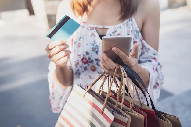 Jeune femme à l'aide de smartphone avec sacs à provisions et carte de crédit au centre commercial vendredi noir