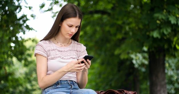 Jeune femme à l'aide de son smartphone sur un banc dans un parc