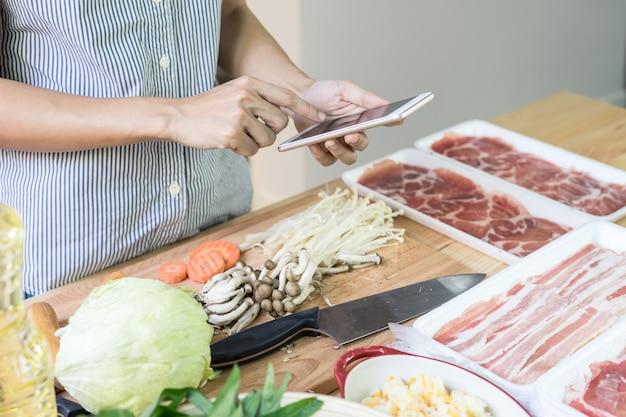 Jeune femme à l'aide de son smartphone dans la cuisine