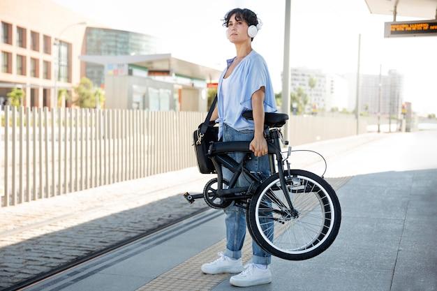 Jeune femme à l'aide de son vélo pliant