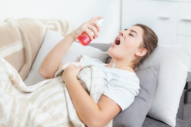 Jeune femme à l'aide d'un spray pour la gorge en position couchée sur le canapé