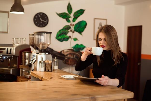 Jeune femme à l'aide de tablette dans un café.