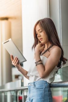 Jeune femme à l'aide de tablette dans l'immeuble de bureaux de lunettes.