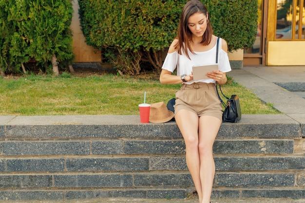 Jeune femme à l'aide de tablette numérique dans une rue par une journée ensoleillée