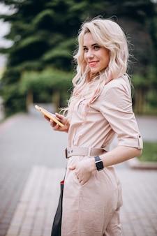 Jeune femme à l'aide de téléphone à l'extérieur dans le parc