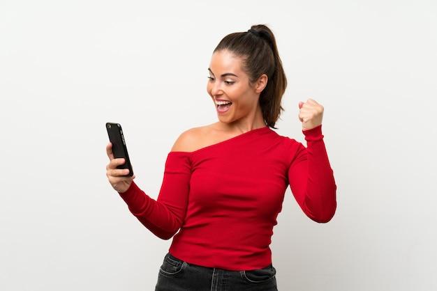 Jeune femme à l'aide d'un téléphone portable célébrant une victoire