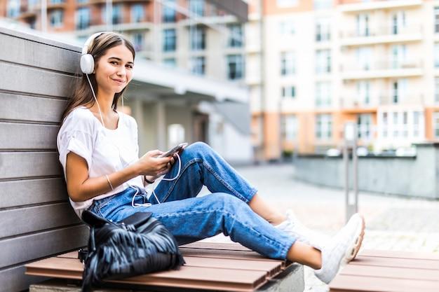 Jeune femme à l'aide de téléphone portable écouter de la musique tout en étant assis sur un banc dans un parc