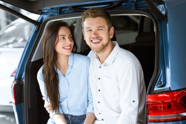 Jeune femme aimante souriant à son mari heureux tout en étant assis ensemble dans le coffre d'une nouvelle voiture
